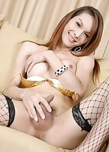 Ladyboy Micky showing her pristine body in a golden bikini and black stockings and playing with her cock
